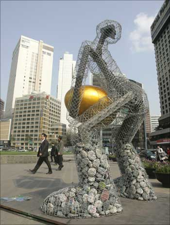 People walk past a statue titled 'Seoul broods a golden egg' at the Seoul city hall plaza in central Seoul, South Korea.