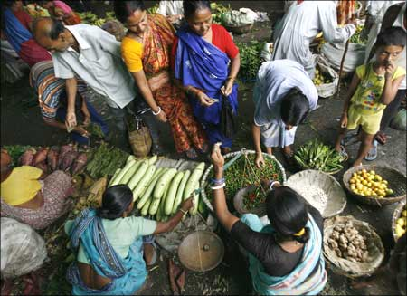 People buy vegetable at a village market.
