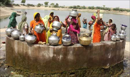 Women gather at a village well to draw drinking water.