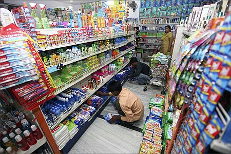 Workers arrange consumable goods as a customer (back) shops at a grocery store in Lucknow.