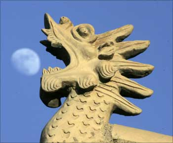 Chinese architecture style dragon head is seen as the moon rises at Jiayuguan Pass, China