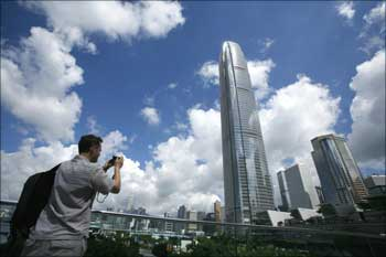 A visitor takes a picture in front of Two IFC, Hong Kong's highest commercial building.