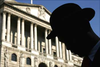 An actor is silhouetted in front of the Bank of England during the filming of a TV programme.