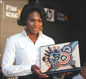 US tennis star Serena Williams holds a laptop during the launch of Hewlett Packard's new imprint design notebooks in New Delhi.