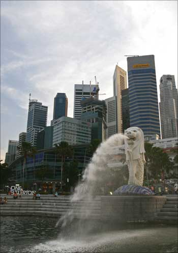 People sit on the steps near the Merlion, in Singapore's financial district.