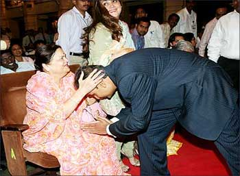 Anil Ambani seeks blessings from mother Kokila Ben as wife Tina Ambani looks on.